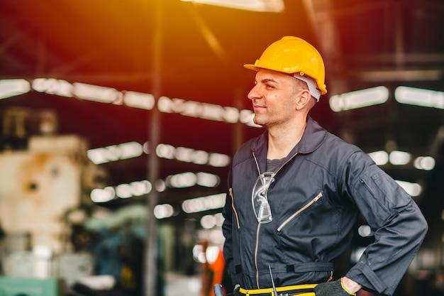 Glücklicher arbeiter, porträtlächeln schöne arbeit mit sicherheitsanzugwerkzeuggürtel und funkdienstmann in der fabrik.