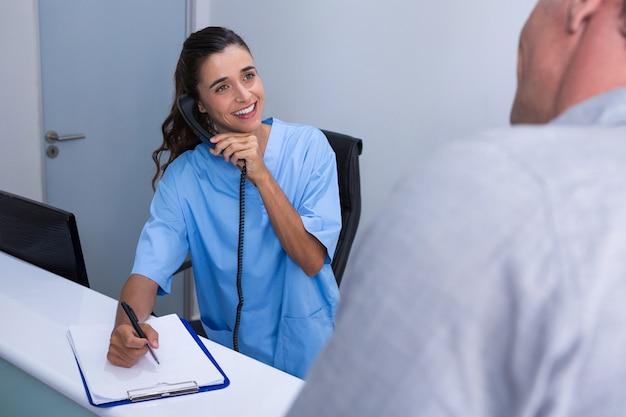 Glücklicher arzt, der am telefon spricht, während patient betrachtet