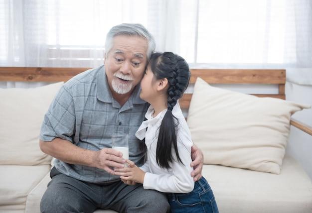 Glücklicher asiatischer älterer älterer großvater hat enkelkind, das sich kümmert und darauf achtet, milch zu geben und auf die wange zu küssen, während man zu hause auf dem sofa sitzt