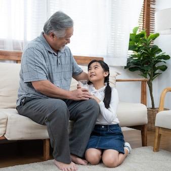 Glücklicher asiatischer älterer älterer großvater hat enkelkind, das sich um milch und kuss auf wange kümmert, während zu hause auf sofa sitzend, ruhestandsgesundheitslebensstilkonzept.