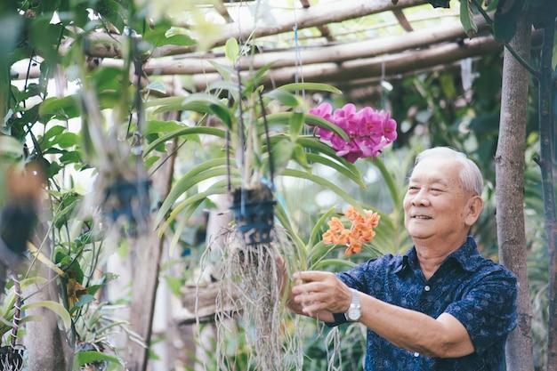Glücklicher asiatischer älterer mann in seinem garten. glückliches rentenalter.