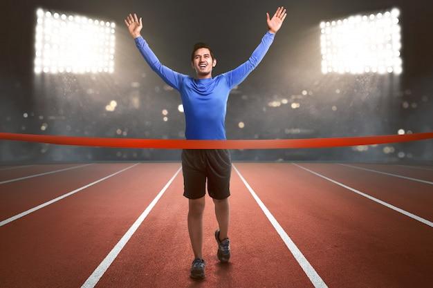 Glücklicher asiatischer athletenmann, der zur ziellinie läuft