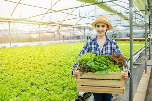 Glücklicher asiatischer bauerngärtnerhandhandkorb des frischen grünen organischen gemüses im gewächshaushydroponik-bio-bauernhof, kleinunternehmerunternehmerkonzept