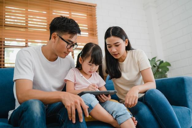 Glücklicher asiatischer familienvater, mutter und tochter unter verwendung der computer-tablet-technologie, die sofa im wohnzimmer am haus sitzt