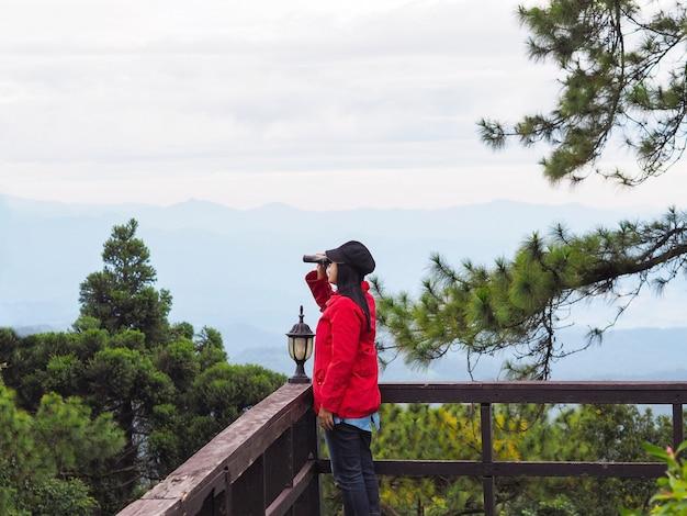 Glücklicher asiatischer frauentourist, der durch fernglas über bergblick mit nebel im morgenhintergrund schaut