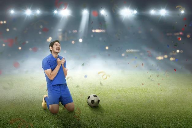 Glücklicher asiatischer fußballspieler, nachdem ein ziel erzielt worden ist