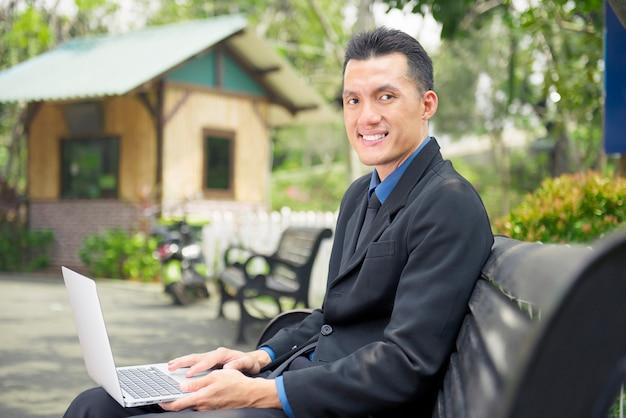 Glücklicher asiatischer geschäftsmann, der laptop sitzt und verwendet