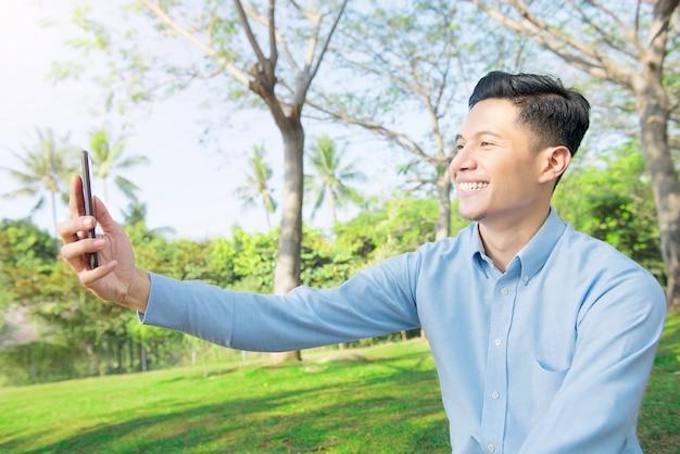 Glücklicher asiatischer geschäftsmann mit dem lächeln, das ein selbstfoto macht