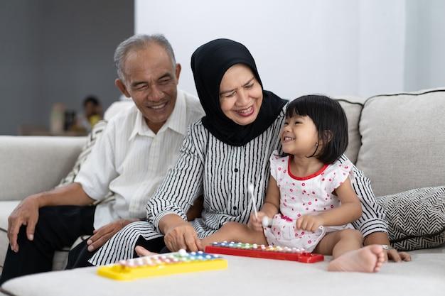 Glücklicher asiatischer großelternteil, der spaß mit enkelkind hat