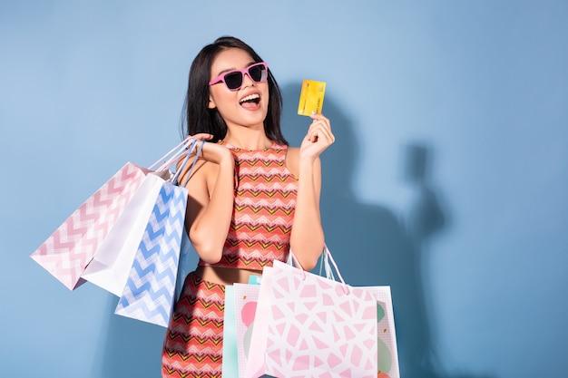 Glücklicher asiatischer hübscher mädchensommer, der einkaufstaschen während griff-kreditkarten und sonnenbrille weg schauen hält