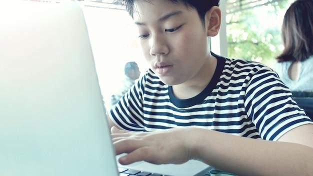 Glücklicher asiatischer junge, der auf laptop-computer schreibt.