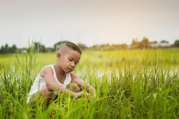 Glücklicher asiatischer junge, der ein weißes hemd spielt auf dem grünen bauernhofgebiet in der sommerzeit trägt.