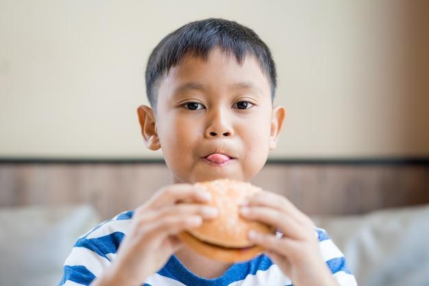 Glücklicher asiatischer junge, der hamburger in der gaststätte isst