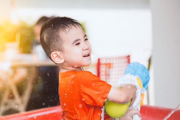 Glücklicher asiatischer junge des kleinen kindes, der spaß hat, wasser mit wasserwerfer und in songkran-festi zu spielen