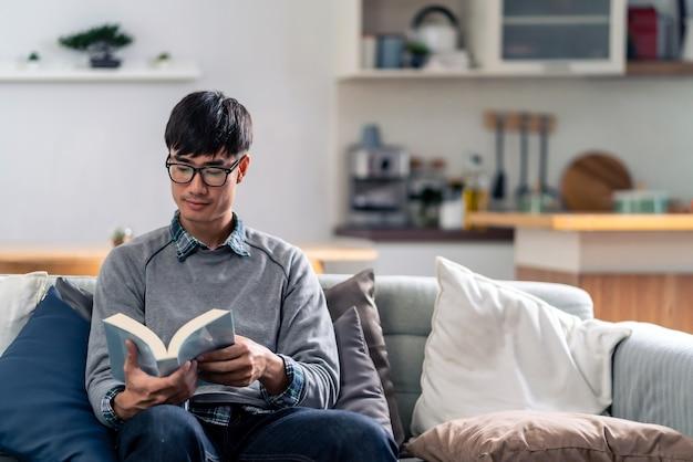 Glücklicher asiatischer junger erwachsener mann, der auf sofa am wohnzimmer sitzt, das fiktionsbuch liest.