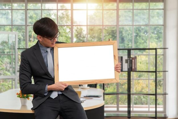 Glücklicher asiatischer junger geschäftsmann, der ein leeres weißes brett hält