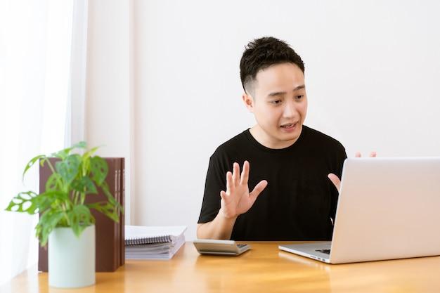 Glücklicher asiatischer junger geschäftsmann im entspannten lässigen stil, der eine videokonferenz mit seinem kollegen durchführt, online-besprechung und videokonferenz verwendend, um covid-19-pandemie zu vermeiden. neue normale lebensstile.