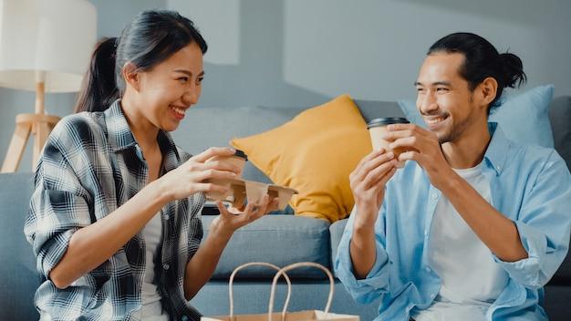 Glücklicher asiatischer junger paarmann und -frau sitzen am neuen haus, trinken kaffee und sprechen mit kartonverpackungsbox-lagerung