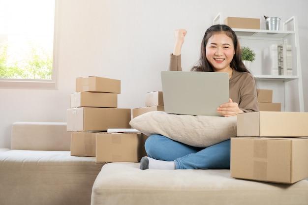Glücklicher asiatischer junger unternehmer, lächeln für verkaufserfolg, nachdem bestellung vom on-line-einkaufsspeicher überprüft worden ist