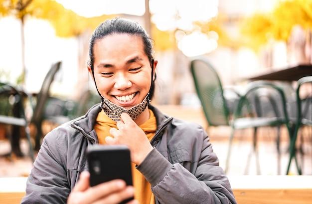 Glücklicher asiatischer kerl, der mit offener gesichtsmaske nach wiedereröffnung der sperre lächelt