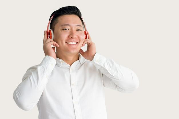 Glücklicher asiatischer kerl, der musik in den kopfhörern hört
