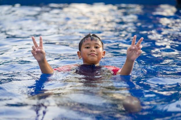 Glücklicher asiatischer kinderjunge, der auf swimmingpool im sommer schwimmt
