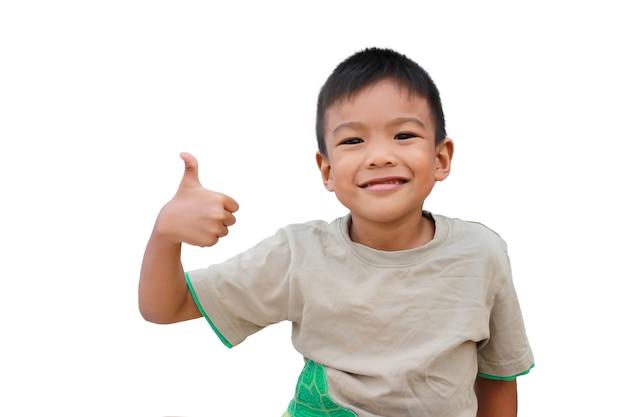 Glücklicher asiatischer kinderjunge, der daumen oben zeigt. auf einem weißen hintergrund.