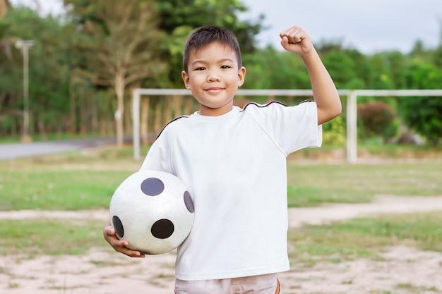 Glücklicher asiatischer kinderjunge, der ein fußballspielzeug in seinen händen spielt und hält er trägt weißes hemd auf dem feldspielplatz glücklicher und lächelnder junge