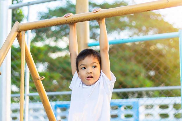 Glücklicher asiatischer kinderjunge, der von einer stahlstange am spielplatz spielt und hängt.