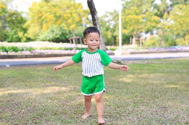 Glücklicher asiatischer kleiner junge, der barfuß auf gras im sommergarten geht.