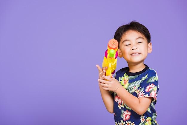 Glücklicher asiatischer kleiner junge, der plastikwasserpistole, thailand songkran festivaltag hält