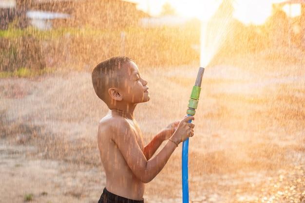 Glücklicher asiatischer kleiner junge, der wasser vom schlauch spielt