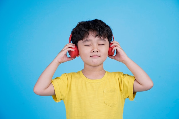 Glücklicher asiatischer kleiner junge mit kopfhörern hören musik