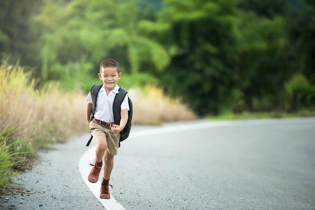 Glücklicher asiatischer kleiner junge zur schule gehen