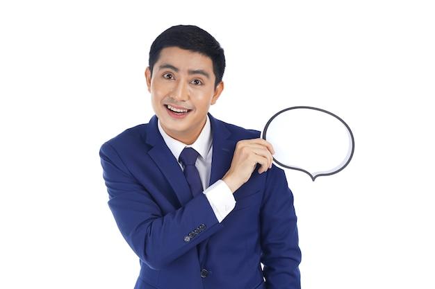 Glücklicher asiatischer lächelnder junger geschäftsmann, der blasensprache hält, lokalisiert auf weißem hintergrund