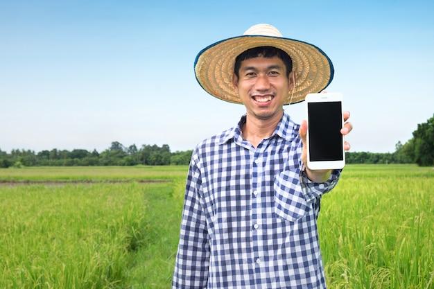 Glücklicher asiatischer landwirtmann, der den smartphone schaut kamera verwendet. havest reisfarm mit technologie