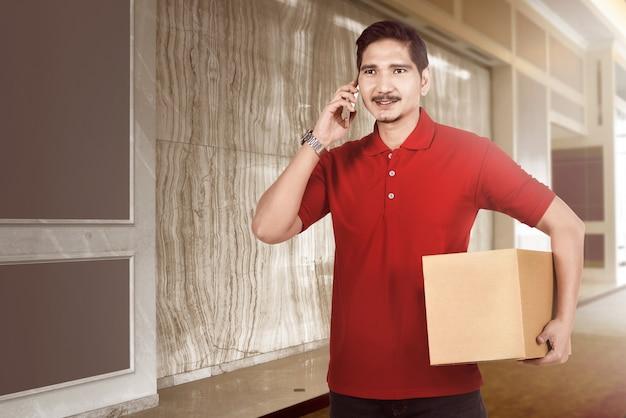 Glücklicher asiatischer lieferbote mit paket unter verwendung des mobiltelefons