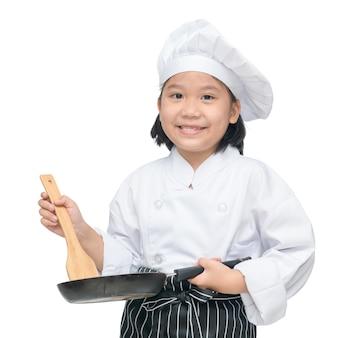 Glücklicher asiatischer mädchenchef, der kochgeräte und das lächeln lokalisiert auf weißem hintergrund hält