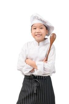 Glücklicher asiatischer mädchenkoch in der uniform, die holzlöffel lokalisiert auf weiß hält