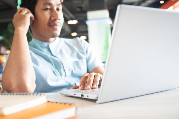 Glücklicher asiatischer männlicher aufpassender film durch laptop-computer. technologie nutzen