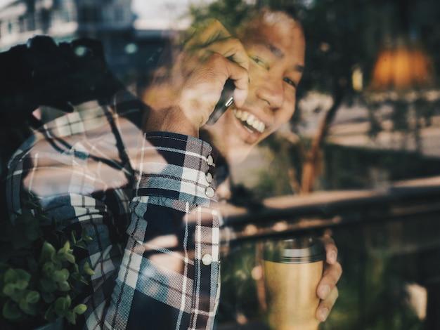 Glücklicher asiatischer mann, der am telefon in der kaffeestube spricht.