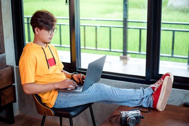 Glücklicher asiatischer mann, der an einem kaffeehaus auf laptop arbeitet