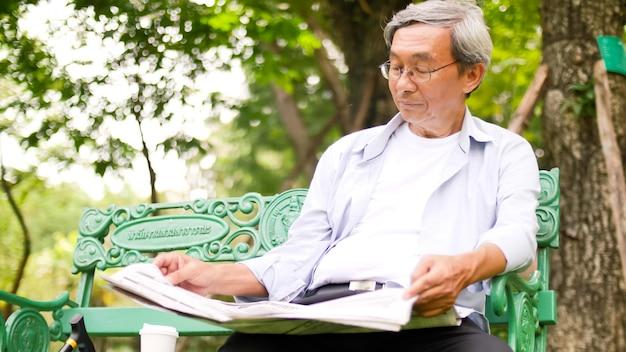 Glücklicher asiatischer mann, der auf einer bank sitzt und eine zeitung im park liest.