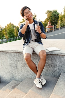 Glücklicher asiatischer mann, der auf handy spricht, während draußen mit tasse kaffee sitzt