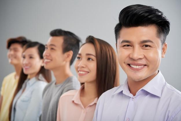 Glücklicher asiatischer mann, der die kamera steht im vordergrund seiner kollegen betrachtet