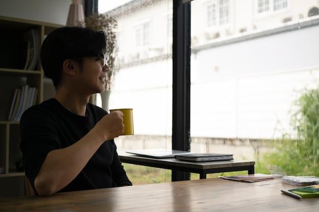 Glücklicher asiatischer mann, der eine tasse kaffee hält und aus dem fenster schaut.