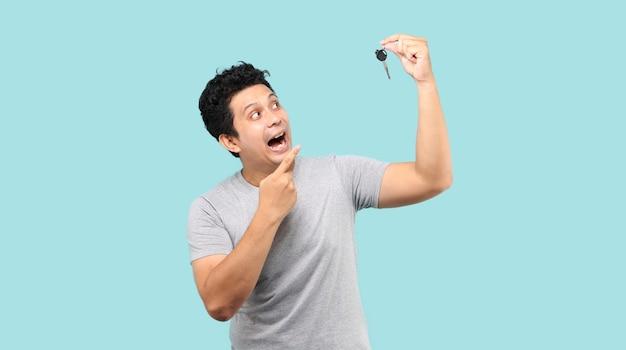 Glücklicher asiatischer mann, der einen autoschlüssel hält und darauf zeigt
