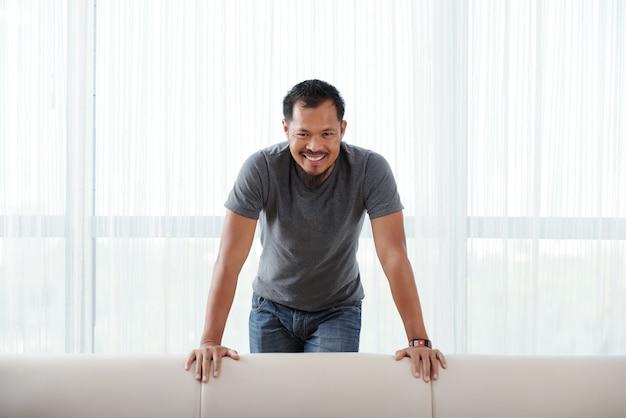 Glücklicher asiatischer mann, der hinter couch steht, auf ihr sich lehnt und für kamera lächelt