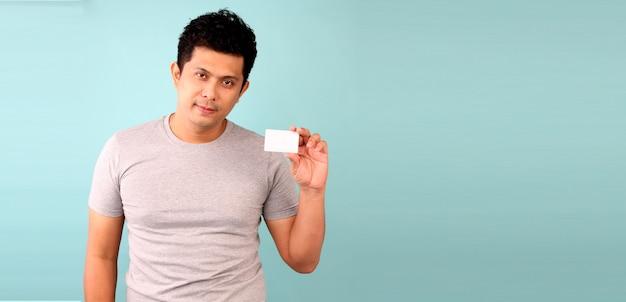 Glücklicher asiatischer mann, der kreditkarte auf einem blauen hintergrund hält