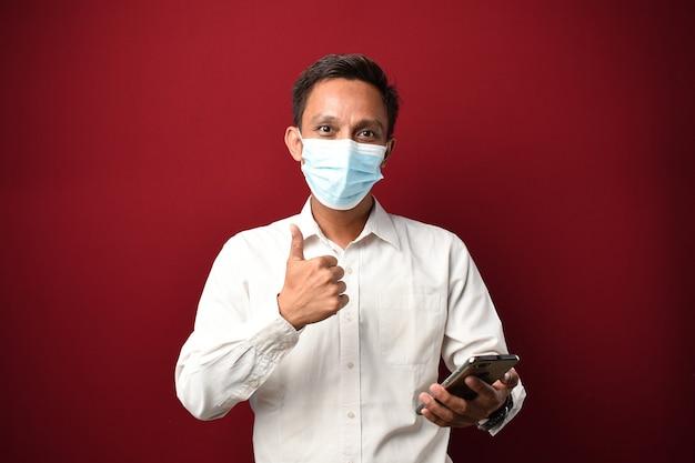 Glücklicher asiatischer mann, der medizinische maske mit smartphone mit schilddaumen mit den fingern trägt.